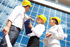 below view of business partners in helmets looking at modern office building - stock photo