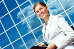 Image of pretty businesswoman with clipboard on background of modern building ou Stock Photos