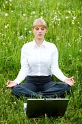 Portrait of businesswoman sitting on the grass and meditating Stock Photos