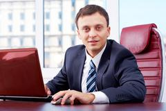 Portrait of smart businessman looking at camera with laptop near by Stock Photos