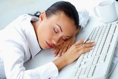 image of young businesswoman sleeping on workplace with her head on keyboard - stock photo