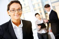 Stock Photo of portrait of cheerful woman in eyeglasses on the background of communicating peop