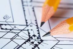 Close-up of blueprints with sketch of project on workplace and two pencils Stock Photos