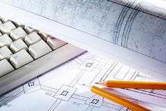 close-up of blueprints with sketches of projects, pencils and computer keypad - stock photo