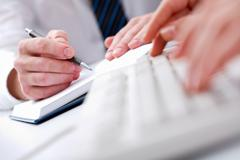 close-up of male hands writing in notepad with typing secretary hands in front o - stock photo