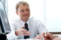 Portrait of businessman explaining work to his colleague Stock Photos
