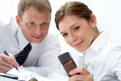 portrait of busy companions looking at cellphone during discussion - stock photo
