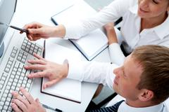 Photo of female pointing at monitor with typing man near by during discussion Stock Photos