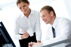 Successful businessman looking at monitor with his pretty colleague near by Stock Photos