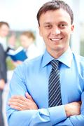 portrait of handsome businessman smiling at camera in working environment - stock photo