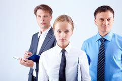 Portrait of serious businesswoman looking at camera with colleagues behind Stock Photos