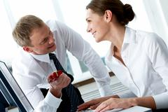 Successful businessman looking at his secretary while giving her small giftbox i Stock Photos