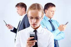 Portrait of serious businesswoman and two men with cellular phones Stock Photos