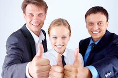 Image of happy business people showing thumbs up and smiling Stock Photos