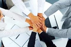 Above angle of business partners making pile of hands over workplace Stock Photos