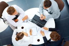 above view of several business people planning work at round table - stock photo