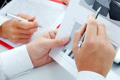 Close-up of businessman hand pointing at diagram during discussion Stock Photos