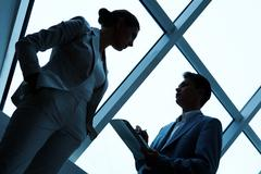 Two silhouettes of businesspeople interacting with each other in the office Stock Photos