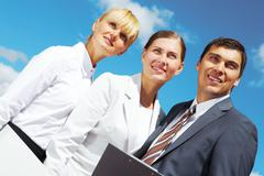 Portrait of confident business people on background of cloudy sky Stock Photos
