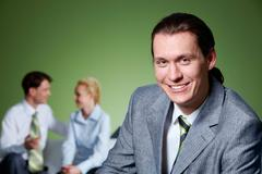Portrait of people interacting with smiling businessman in front looking at came Stock Photos
