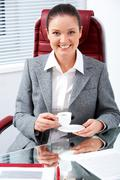 Portrait of happy professional with cup in hand looking at camera with smile in Stock Photos