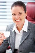 portrait of happy professional with cup of coffee in hand looking at camera with - stock photo
