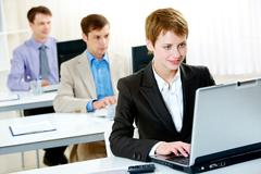 Row of employees typing on the laptop with woman in front Stock Photos