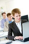 pretty employee typing on background of working colleagues in the office - stock photo