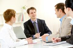 portrait of businessman explaining work to his colleagues in office - stock photo