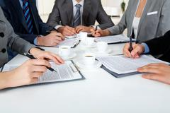 Image of business people hands with ballpoints writing on papers while planning Stock Photos
