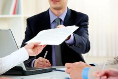 Close-up of handing over documents during business briefing Stock Photos