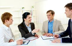 Portrait of businesswoman explaining work to colleagues in the boardroom Stock Photos