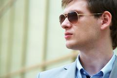 handsome businessman looking through sunglasses outside - stock photo