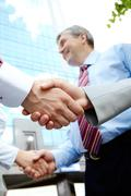 vertical image of rows of partners handshaking outdoors on background of modern - stock photo