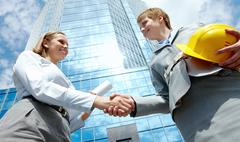 Image of two businesswomen handshaking at background of modern office building Stock Photos