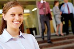 portrait of pretty employee smiling at camera with her partners on background - stock photo