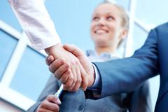 photo of successful associates handshaking after striking deal outdoors at meeti - stock photo