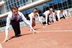 confident business people lined up getting ready for race - stock photo