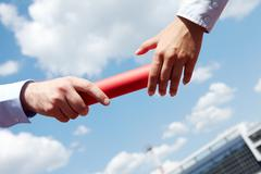 Photo of business people hands passing baton during marathon Stock Photos