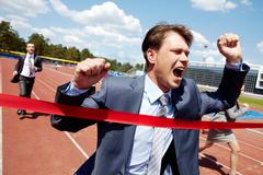 Photo of happy businessman crossing finish line during race Stock Photos