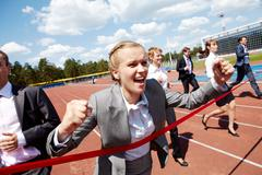 Photo of happy businesswoman crossing finish line during race Stock Photos