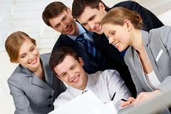 Portrait of friendly workteam looking at monitor of laptop while discussing new Stock Photos
