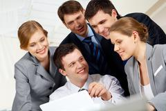 Portrait of friendly workteam looking at monitor of laptop while confident busin Stock Photos
