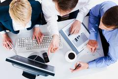 Stock Photo of above view of business people discussing computer work
