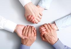 above view of business partners hands holding each other symbolizing support - stock photo