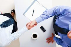 above view of businessman and businesswoman shaking hands over table - stock photo