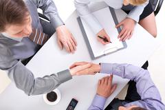Above view of businessmen doing agreement with woman near by Stock Photos