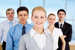 Stock Photo of portrait of pretty leader looking at camera with business team behind