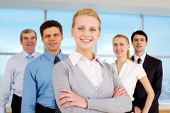 Portrait of pretty leader looking at camera with business team behind Stock Photos