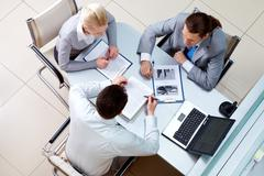 view from above of business team sitting at table in the office and communicatin - stock photo